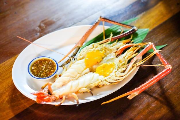 Piec na grillu gigantyczna rzeczna krewetka z korzennym owoce morza ustawiającym na drewnianym stole przy ayutthaya tajlandia (garnele) - domowej roboty karmowy pojęcie.