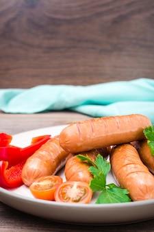 Piec na grillu kiełbasy z warzywami na talerzu na drewnianym stole