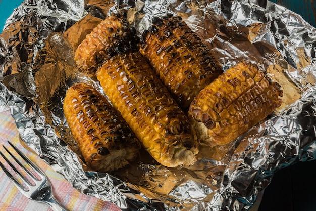 Piec na grillu kukurudza na folii nad starym błękitnym drewnianym stołem