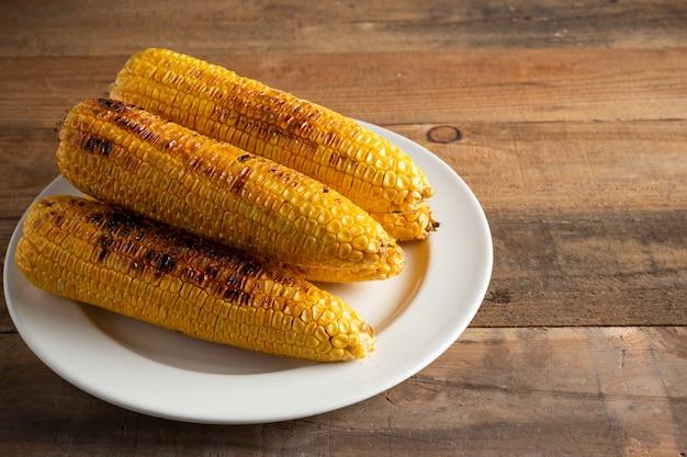 Piec na grillu kukurydzani cobs na drewnianym tle.