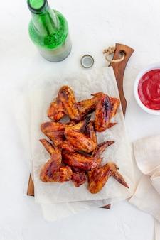 Piec na grillu kurczaków skrzydła i piwo na białym tle. przekąska do piwa. grill. przepisy