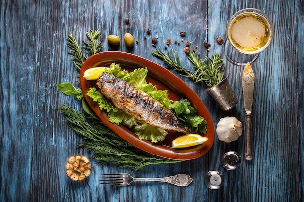 Piec na grillu makrela przepasuje z cytryną na nieociosanym tle