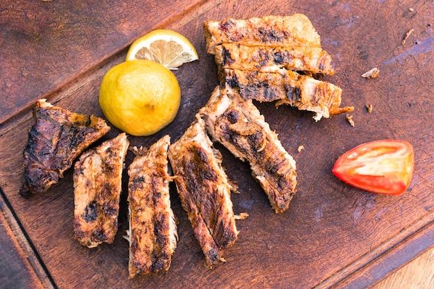 Piec na grillu mięso i pokrojony cytryna pomidor na stole