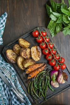 Piec na grillu warzywa na tnącej desce na ciemnym drewnianym tle