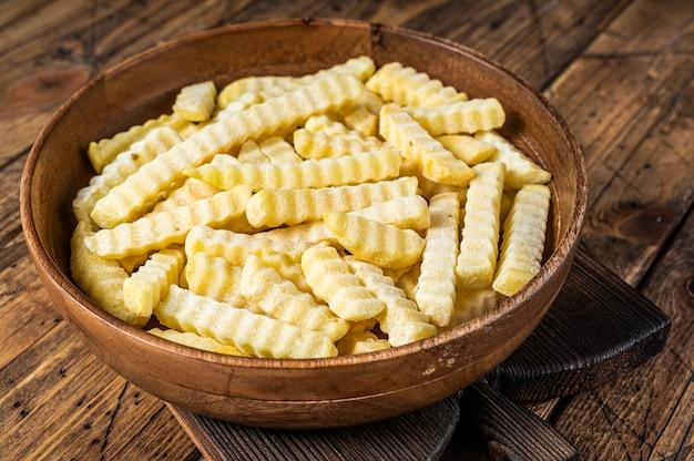 Piec na zimno frozen crinkle frytki ziemniaczane w drewnianym talerzu. drewniane tło. widok z góry.