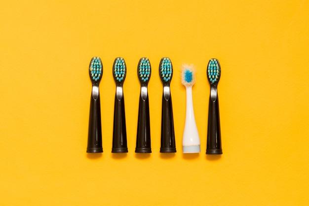 Pięć nowych czarnych szczoteczek do zębów i jedna stara biała szczoteczka do zębów na żółtym tle