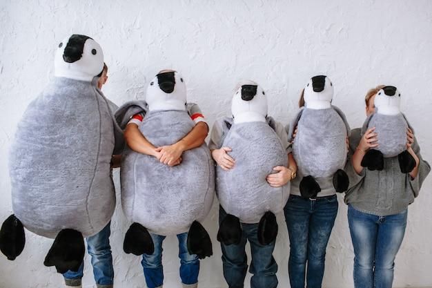 Pięć osób ukrywa twarze za wypchanymi lalkami pingwina