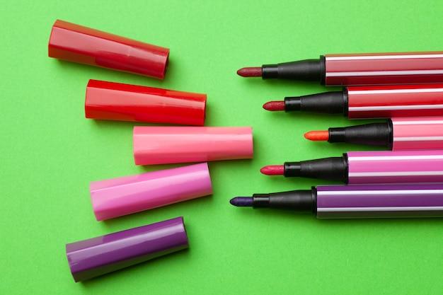 Pięć otwartych markerów lub długopisów w różowym, fioletowym i różowym kolorze leży jak kroki na zielonym