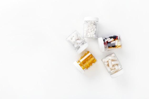 Pięć paczek z różnorodnymi pigułkami na białym tle. koncepcja zdrowia. widok z góry z miejsca kopiowania.