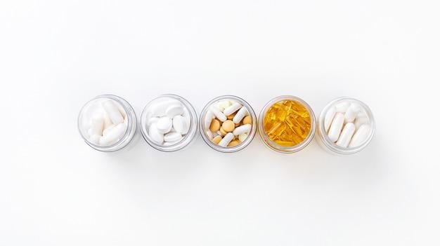 Pięć paczek z różnymi białymi i złotymi pigułkami na białym tle. koncepcja zdrowia. widok z góry z miejsca kopiowania.