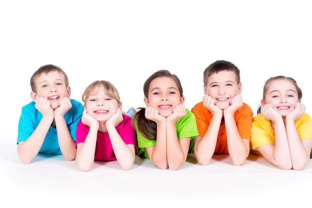 Pięć pięknych uśmiechniętych dzieci leżących na podłodze w jasnych kolorowych koszulkach - na białym tle.