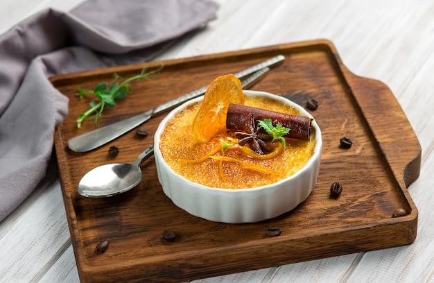 Piec pomarańczowy creme brulee deser w białym pucharze z cynamonem i mennicą na drewnianym tle
