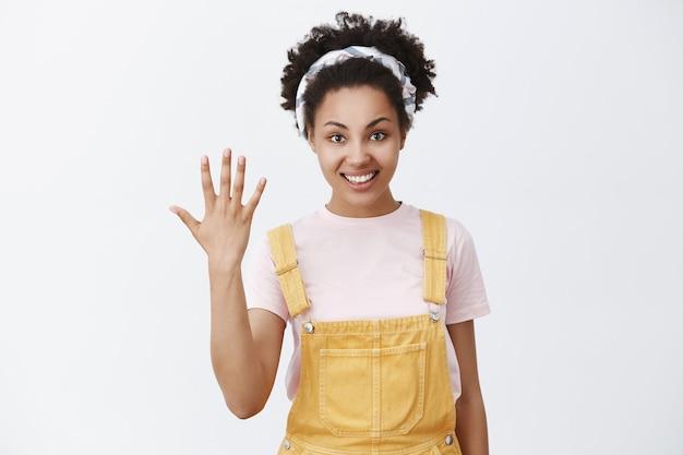 Pięć powodów, by powiedzieć tak. portret przystojnej, szczęśliwej i zrelaksowanej młodej afroamerykanki w żółtych ogrodniczkach i modnej opasce pokazującej dłoń lub piąte miejsce, które zajęła w konkursie