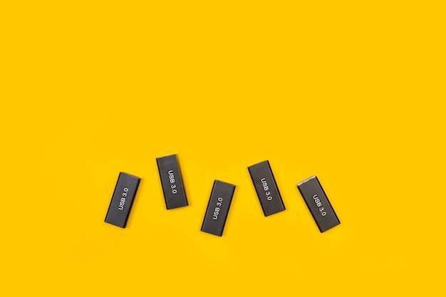 Pięć przenośnych pamięci usb na żółtym tle