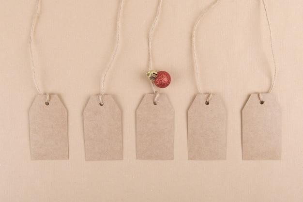 Pięć przywieszek z przetworzonego papieru pakowego do pakowania zawieszonych na sznurku ozdobionym czerwoną bombką