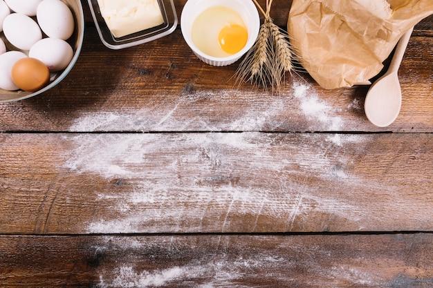 Piec składniki na drewnianym stole z białą mąką