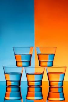 Pięć szklanek z wodą na niebieskim i pomarańczowym tle.