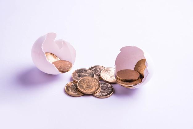 Pięć złotych monet indyjskich rupii wyłaniających się z rozbitego jajka, odizolowane na białym tle