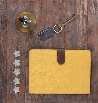 Pięciogwiazdkowy dzwonek hotelowy i klucz hotelowy na drewnianym stole