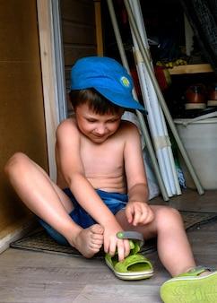 Pięcioletni chłopiec na podłodze zakłada sandały na nogi.