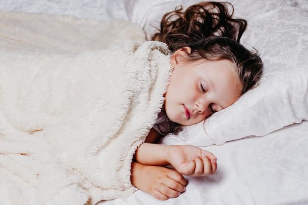 Pięcioletnia dziewczynka śpi spokojnie na poduszce ortopedycznej, domowy komfort i ciepło, zdrowy sen.