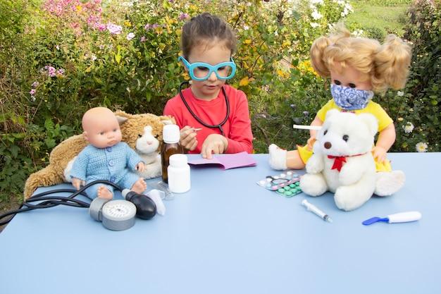 Pięcioletnia dziewczynka w niebieskich okularach bawi się na ulicy w lekarzu
