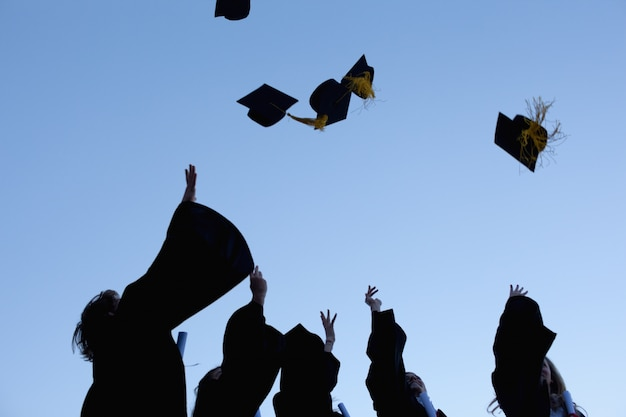 Pięciu absolwentów rzucających kapelusze na niebie