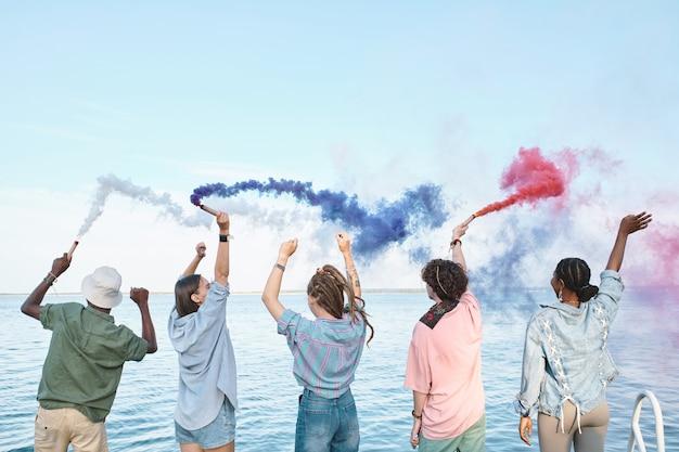 Pięciu ekstatycznych przyjaciół z kolorowymi petardami bawi się nad wodą