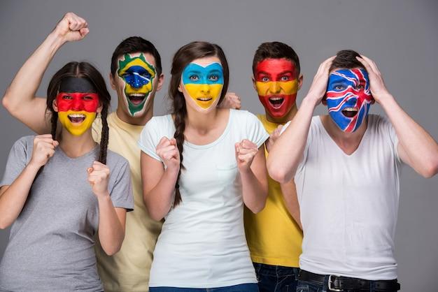 Pięciu emocjonalnych młodych ludzi z flagami narodowymi.
