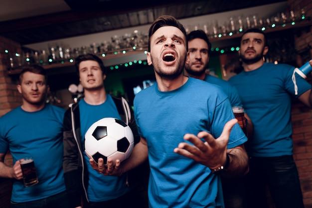 Pięciu fanów piłki nożnej smutnych, że ich drużyna przegrywa w barze