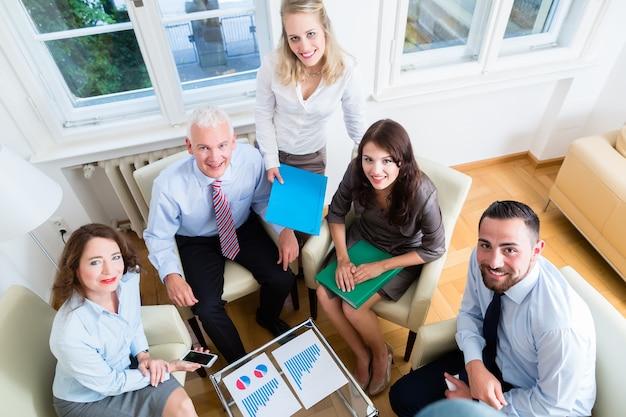 Pięciu ludzi biznesu na spotkaniu zespołu w biurze, studiując wykresy i liczby
