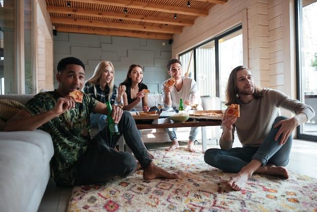 Pięciu przyjaciół siedzi w domu i je pizzę