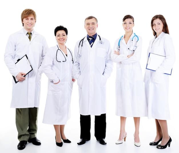 Pięciu szczęśliwych pomyślnych uśmiechniętych lekarzy stojących razem w rzędzie