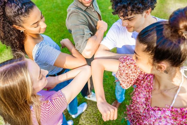 Pięciu wielorasowych przyjaciół w kręgu podskakujących łokciem, witających się za szacunek dla dystansu społecznego