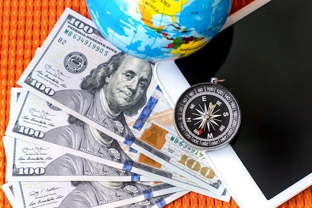 Pięćset dolarów amerykańskich, kompas, kula ziemska i tablet cyfrowy. koncepcja podróży.