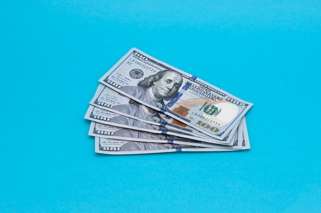 Pięćset dolarów amerykańskich w banknotach po sto dolarów na niebieskiej powierzchni.