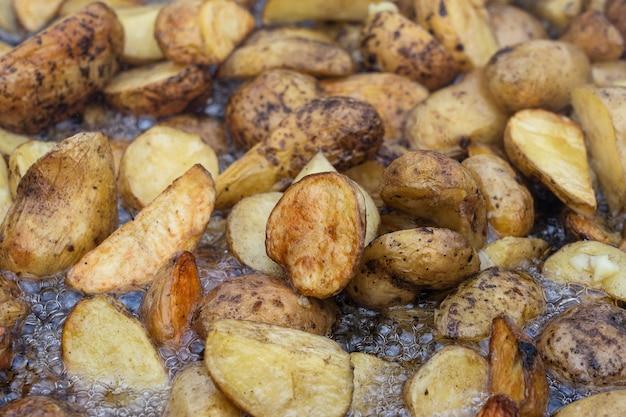 Piecz ziemniaki na dużej patelni. pyszne jedzenie na festiwalu. kuchnia polowa przy palenisku. młode ziemniaki smażone w oleju, street food, ukraina