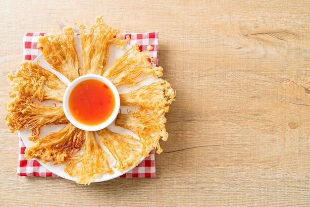 Pieczarka enoki smażona w głębokim tłuszczu lub pieczarka ze złocistymi igłami z pikantnym sosem do maczania - wegańskie jedzenie