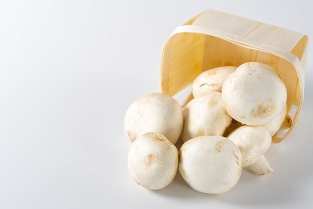 Pieczarki białe grzyby w drewnianym koszu na jasnym tle. zamknij się z miejsca na kopię. zapakowane pieczarki do kosza.
