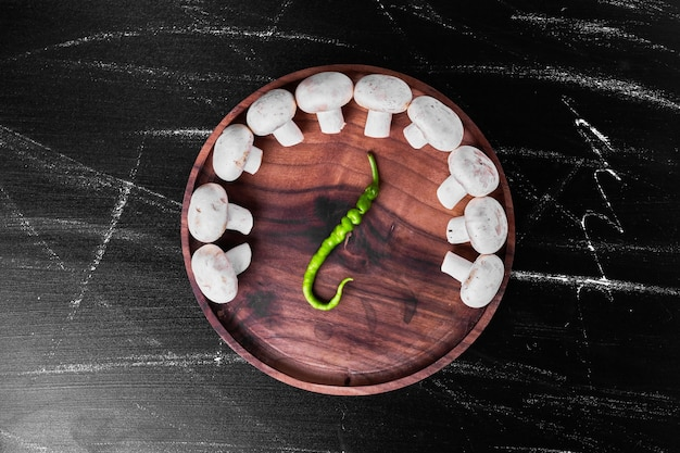 Pieczarki białe z papryczką chili na talerzu.