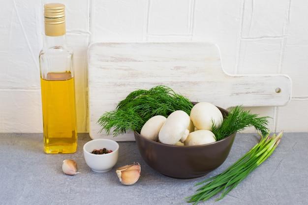 Pieczarki i zioła w misce, deska do krojenia, olej i przyprawy
