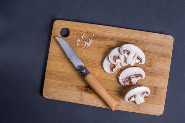 Pieczarki królewskie pieczarki paryskie grzyby na bambusowej drewnianej desce do krojenia układ ciemnego drewnianego tła