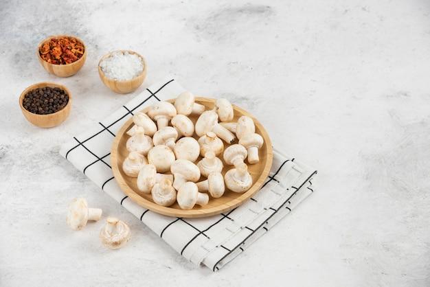 Pieczarki na drewnianym półmisku podawane z różnymi przyprawami.