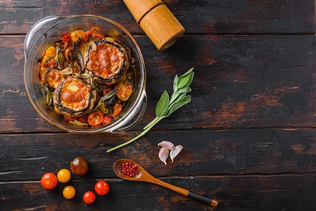 Pieczarki portobello, zapiekane z serem cheddar, pomidorkami cherry i szałwią w szklanym garnku na stare drewniane tło widok z góry miejsca na tekst.