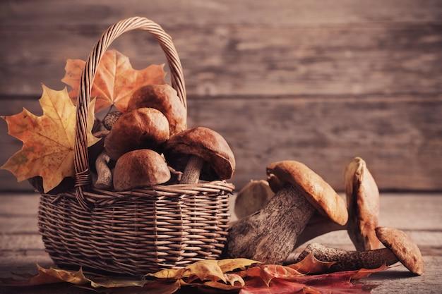 Pieczarki w koszu na drewnianym tle