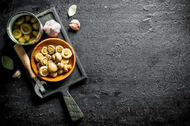 Pieczarki w puszkach na deska do krojenia z ząbkami czosnku i liściem laurowym na czarnym drewnianym stole