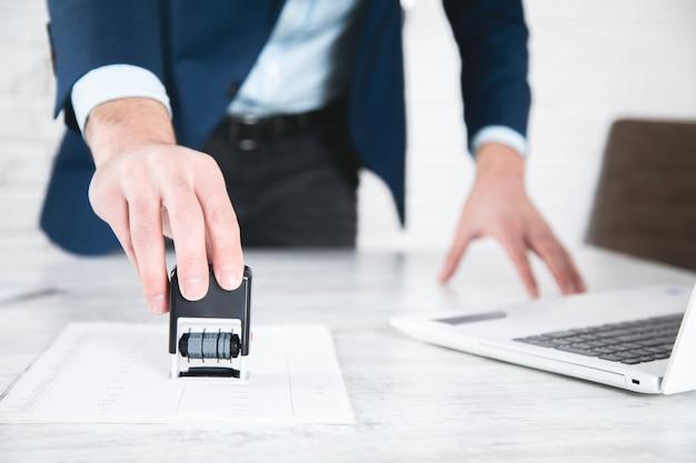 Pieczęć ręka mężczyzny na dokumencie na stole roboczym