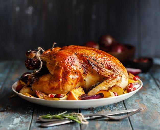 Pieczemy całego kurczaka z pieczonymi warzywami na talerzu na stole