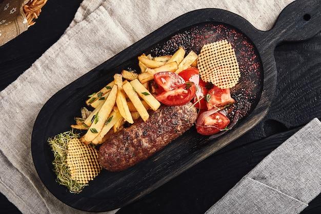 Pieczeń z frytkami i warzywami na desce, tradycyjne angielskie jedzenie. zdjęcie żywności, miejsce na kopię.