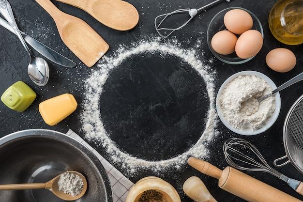 Pieczenia składników do gotowania na czarnym tle. widok z góry. miejsce na kopię ramki.